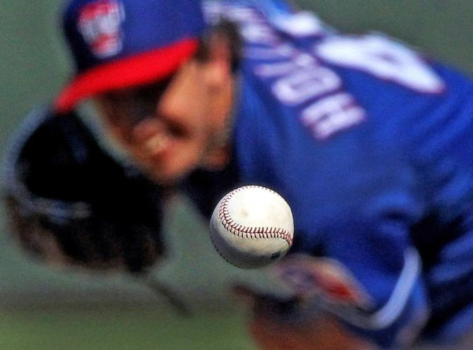 Texas starting pitcher Derek Holland throws a second-inning pitch during the Texas Rangers and Kansas City Royals' first spring training game in Surprise, Ariz.