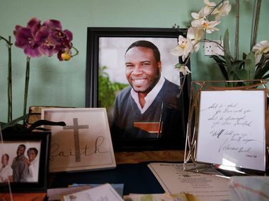 A large photo of Botham Jean with photos and cards is displayed on one of the tables in his childhood home in Castries, St. Lucia on Sept. 25, 2018. Botham Jean was shot and killed in his apartment by off duty Dallas police officer Amber Guyger.