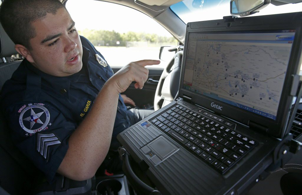 Sgt. Bernardo Garza, of the Wills Point Police Department, talks about a COPsync software inside his patrol car at Forney Community Park in Forney, Texas in this 2016 photo. COPsync software allows officers to access local, state and federal law enforcement databases, gather information at the point of incident and share the data with all other officers on the COPsync Network in their patrol car.