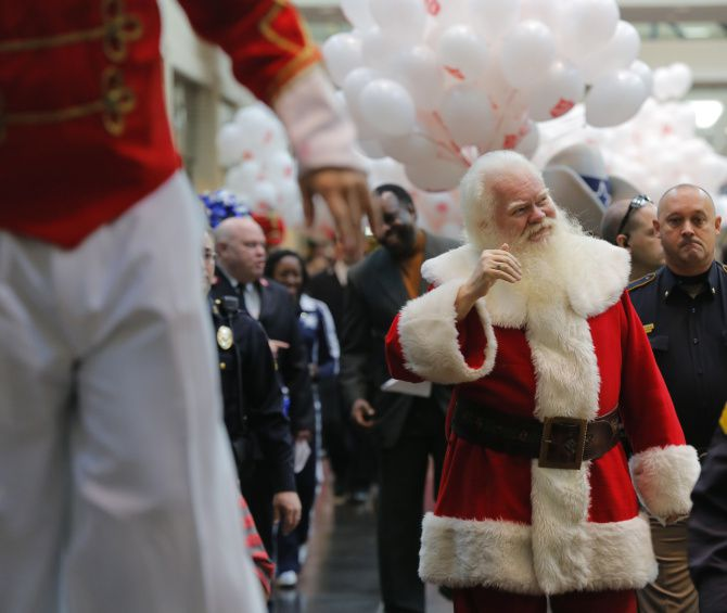 Santa Claus, a.k.a. Carl Anderson, waved to the crowd as a kickoff parade for the Salvation Army's Angel Tree Celebration made its way through NorthPark Center on Black Friday in 2019.