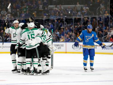 Members of the Dallas Stars celebrate as St. Louis Blues' Ryan O'Reilly, right, skates past following an NHL hockey game Saturday, Feb. 8, 2020, in St. Louis. The Stars won 3-2 in overtime.