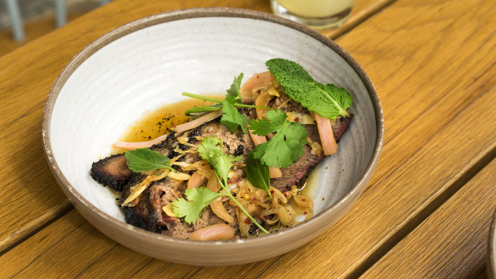 Smoked beef brisket with chili gastrique and Thai herbs is one of the more popular dishes at Loro. It shows off the flavor play between pitmaster Aaron Franklin, of Franklin Barbecue, and chef Tyson Cole, of Japanese restaurant Uchi.