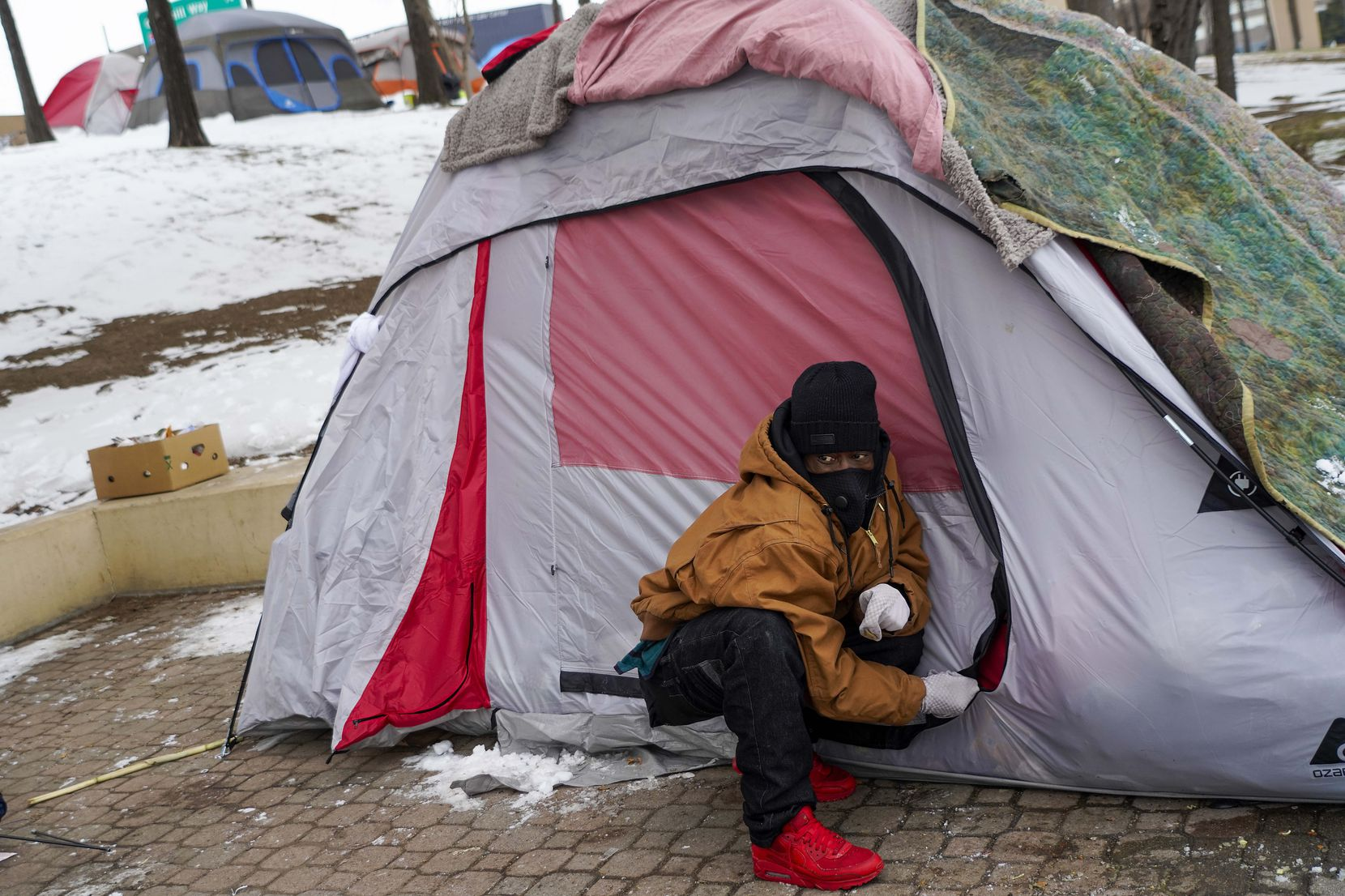 Carlos Jackson zips up the tent he is living in with two other homeless men at Forest Lane and North Central Expressway in Dallas on Tuesday, Feb. 16, 2021.