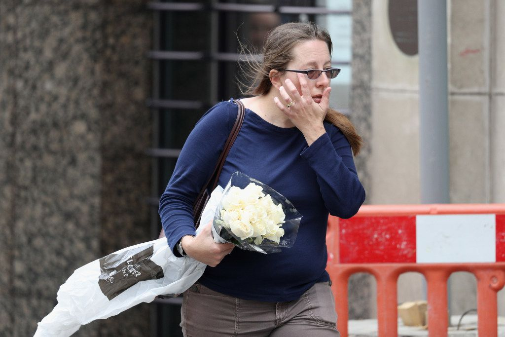 A woman wipes her face as she carries flowers to London Bridge, the scene of last night's terror attack on June 4, 2017 in London, England.
