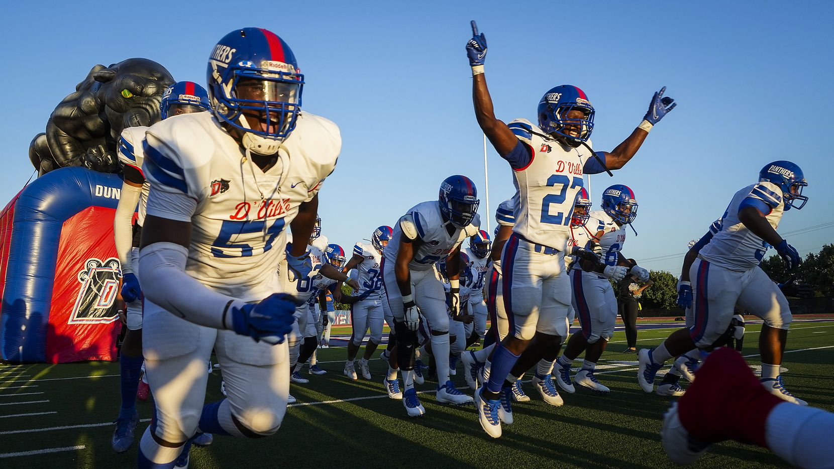 Duncanville players, including defensive lineman Josiah Drake (51) and running back Kaleb Kenney (27) take the field before a high school football game against Mater Dei on Friday, Aug. 27, 2021, in Duncanville.