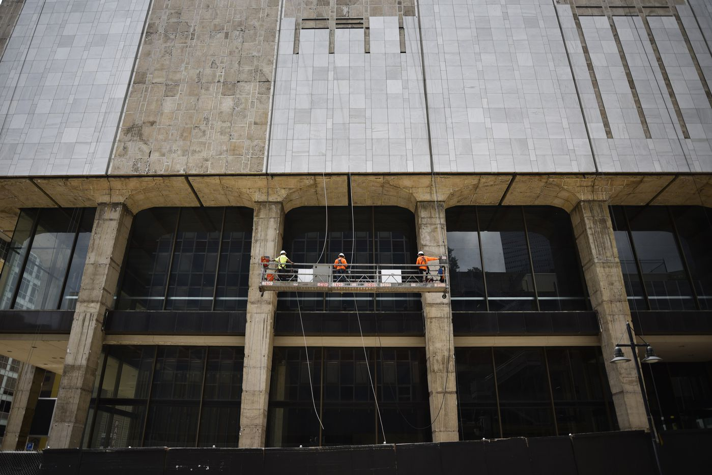 Construction workers use a scaffold to be lifted high above the ground to install marble on the First National Bank building in downtown Dallas.