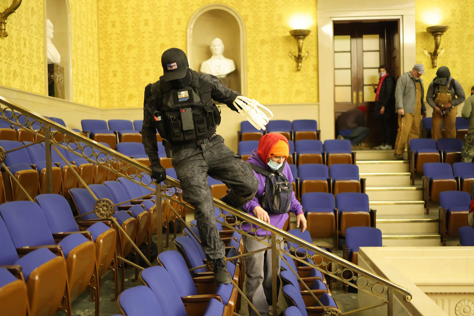 Protesters enter the Senate Chamber on Jan. 6, 2021. Two men photographed carrying zip-ties were charged Sunday in a federal court in the District of Columbia.