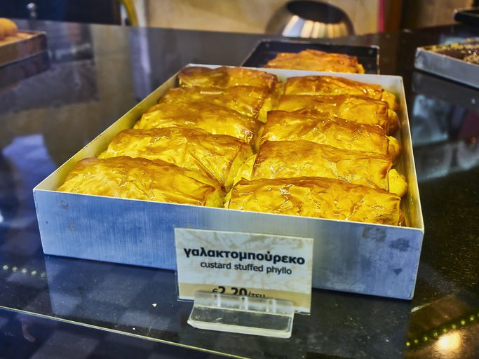 Athens, Greece - June 29, 2018. Galaktoboureko, typical Greek sweet in a storefront of a Greek pastry. Custard stuffed phyllo.