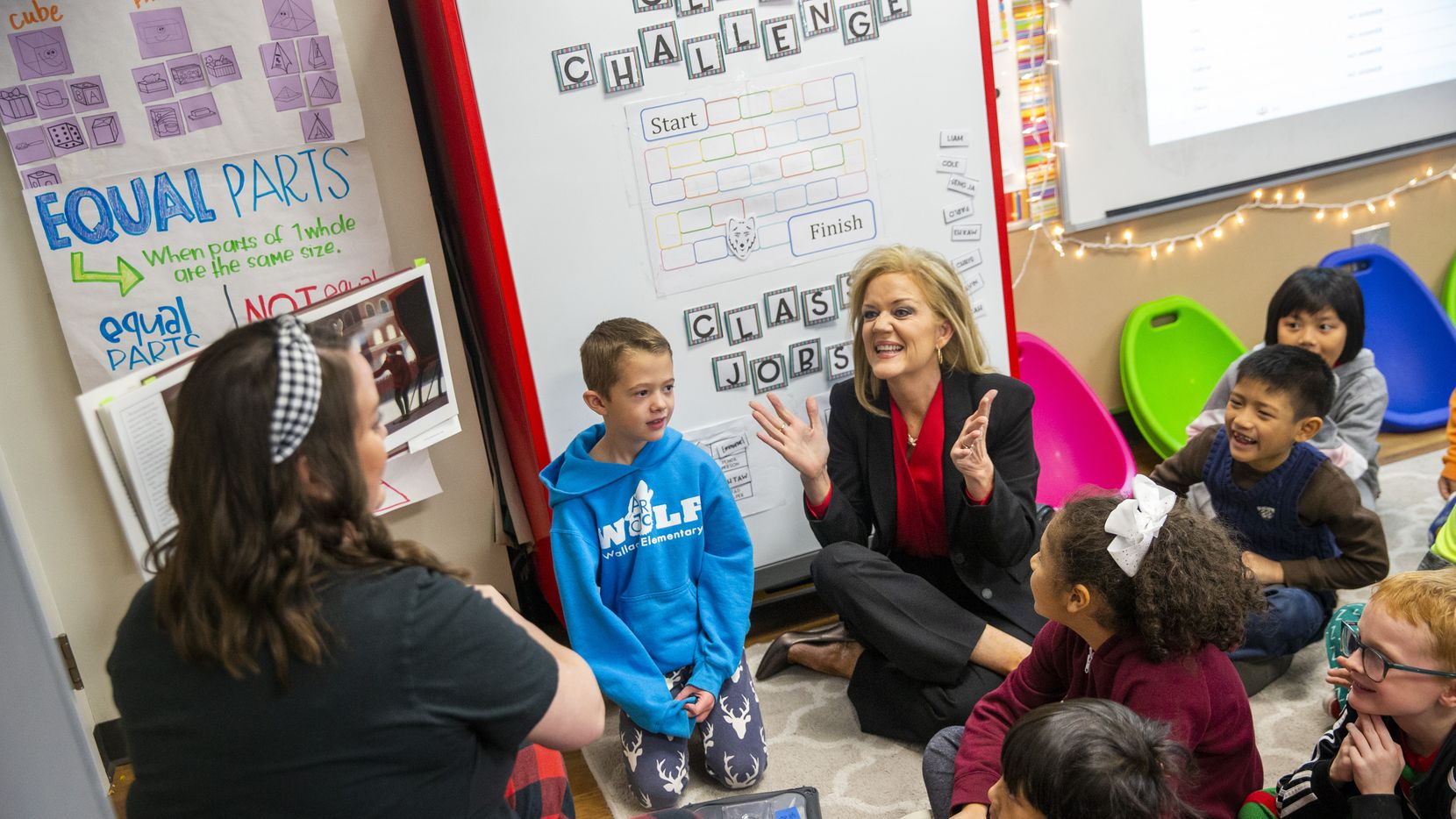 Richardson ISD Superintendent Jeannie Stone (center) reacts with students during a reading of The Polar Express in Kelly Kollaja's second grade classroom at Wallace Elementary School.