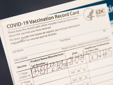 Gladys Rodgers, 77, holds her COVID-19 vaccination card at Fair Park in Dallas on Jan. 14, 2021.
