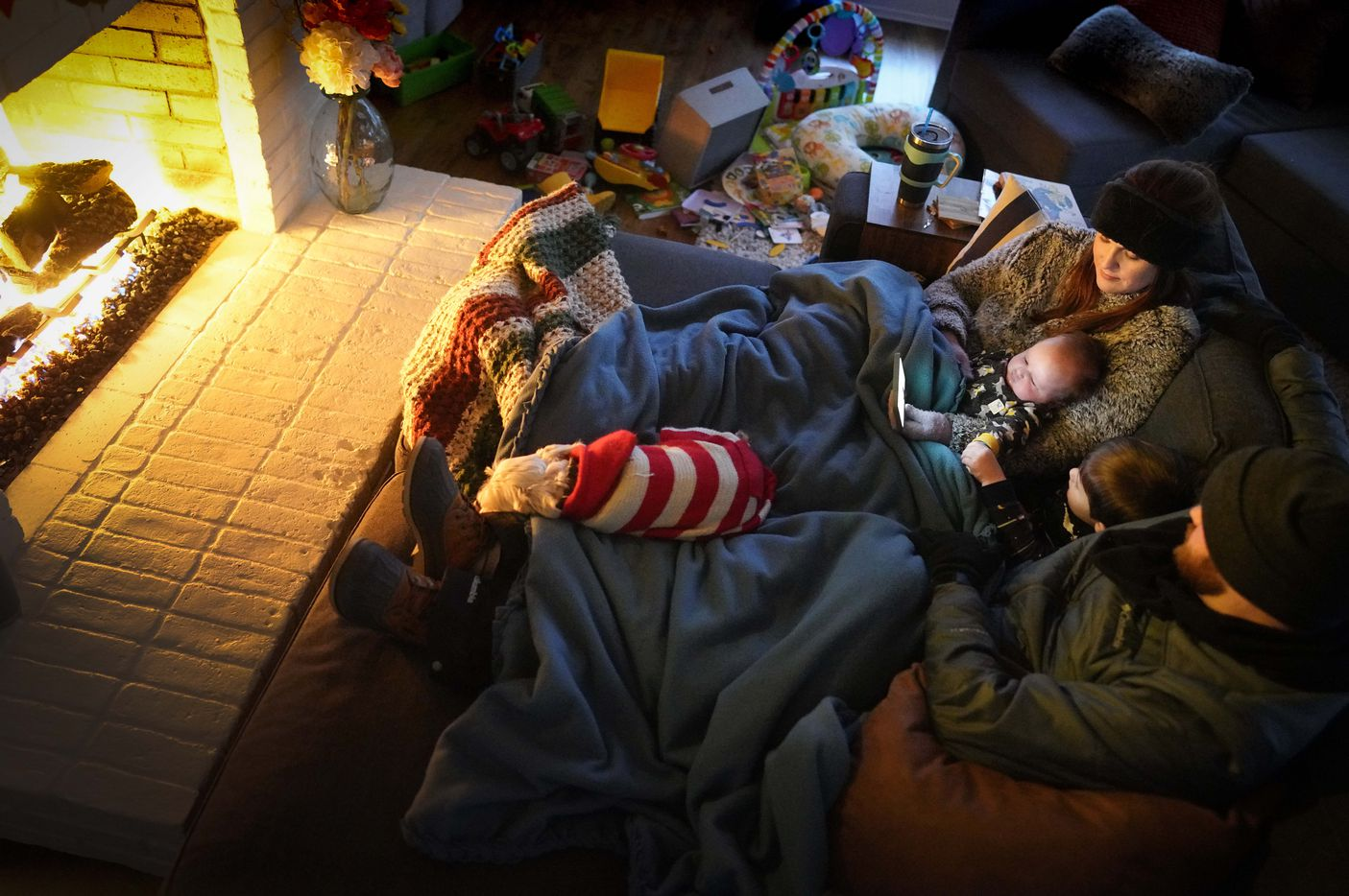 Dan Bryant and his wife Anna huddle by the fire with sons Benny, 3, and Sam, 12 weeks, along with their dog Joey, also wearing two doggie sweaters, with power out and temperatures dropping inside their home after a winter storm brought snow and freezing temperatures to North Texas on Monday, Feb. 15, 2021, in Garland.  The Bryant's, who lost power Monday morning, were wearing outdoor winter clothes, down to snow boots, hat, and ski pants, and even their dog Joey had two doggie sweaters.  More than 2 million Texans were without power after the winter storm prompted outages. (Smiley N. Pool/The Dallas Morning News)