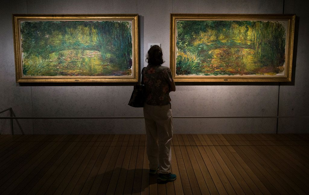 """A museum-goer views """"The Japanese Bridge"""" paintings by Claude Monet as part of the Monet: The Late Years exhibit is seen at Kimbell Art Museum on Friday, June 14, 2019 in Fort Worth, Texas. (Ryan Michalesko/The Dallas Morning News)"""