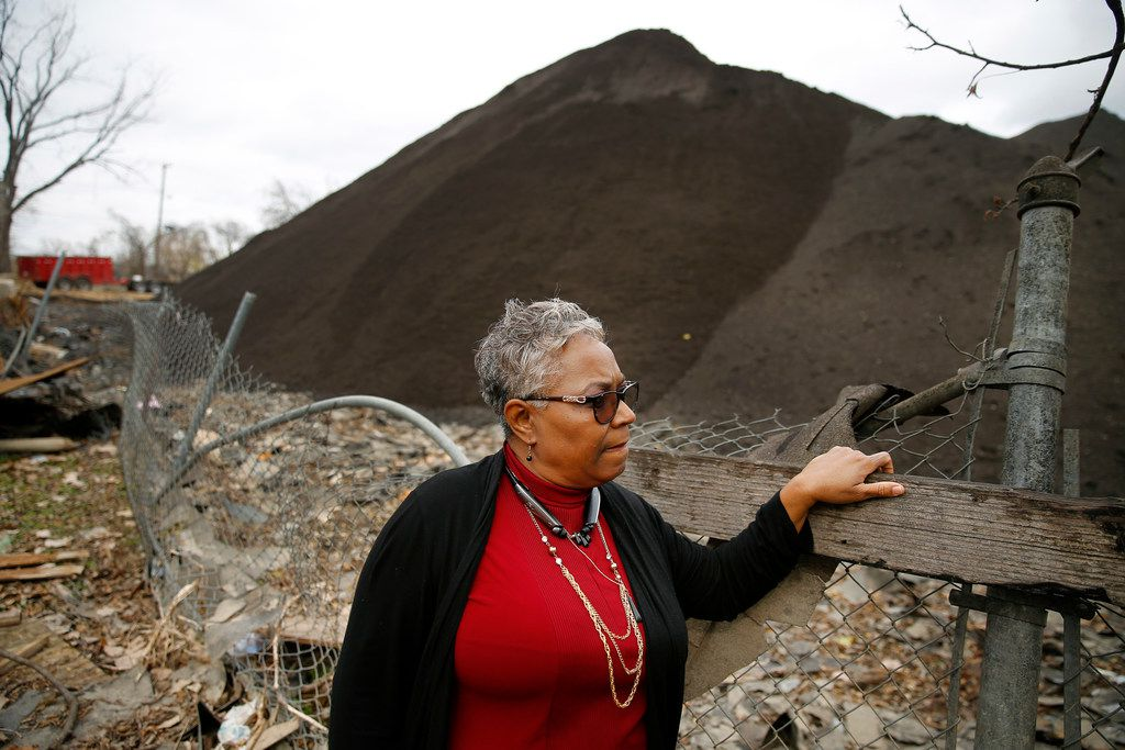 Homeowner Marsha Jackson looks over her damaged fence at the large mounds of shredded roofing shingles.  She is tired of the late night and early morning grinding of shingles that takes place outside her bedroom window in southeast Dallas. The shingle recycling company on South Central Expressway also partially dammed up the watershed that runs behind her house, causing her horse farm to flood. She has since relocated the horses. Along with the shingles, she says, the flooding has destroyed her fences as well.