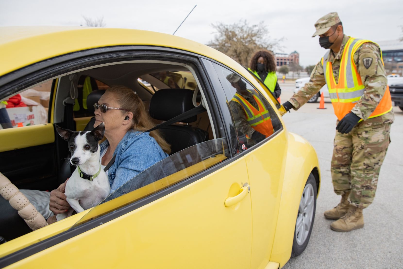 Tina Clark and dog Coco from Fort Worth waited as volunteers and members of the Texas National Guard loaded her car with food from the Tarrant Area Food Bank in a parking lot of Globe Life Field in Arlington on Thursday, Feb. 25, 2021.