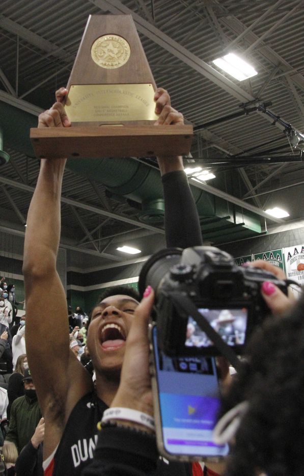 Duncanville's Zhuric Phelps (0) revels in the moment after the Panthers were presented the regional trophy after defeating Waxahachie 70-65 to advance. The two teams played their Class 6A Region ll boys final  playoff basketball game at Waxahachie High School in Waxahachie on March 5, 2021. (Steve Hamm/ Special Contributor)
