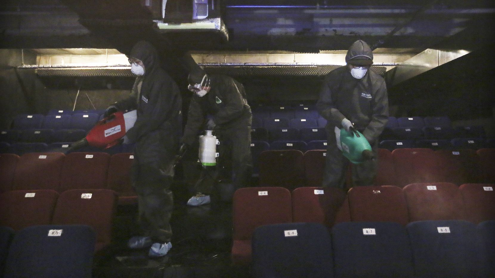 Workers wearing protective gear spray disinfectant as a precaution against a new coronavirus at a theater in Seoul, South Korea, Thursday, Feb. 6, 2020.