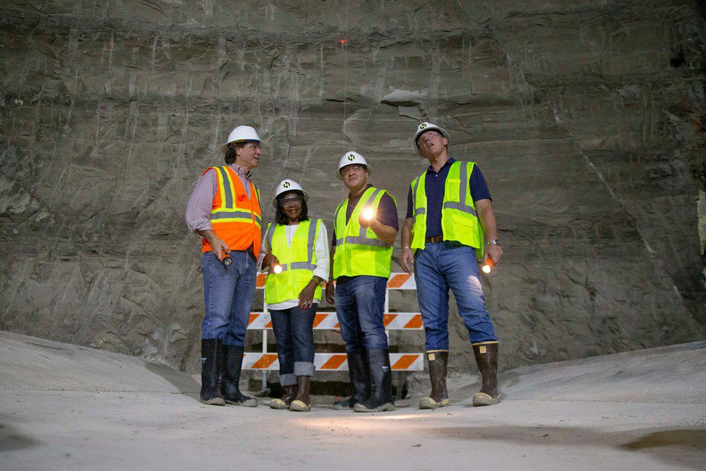 Lee Kleinman (from left), the Dallas City Council member who chairs the transportation and infrastructure committee, visits the tunnel with council colleagues Carolyn King Arnold and Adam Medrano and councilman-elect David Blewett. Behind them is a wall of millions-year-old sediment.