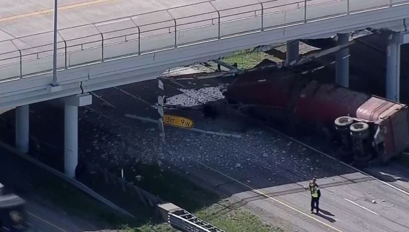 A rock hauler lies on its side after striking an overpass on U.S. Highway 80 in Forney on Wednesday morning.