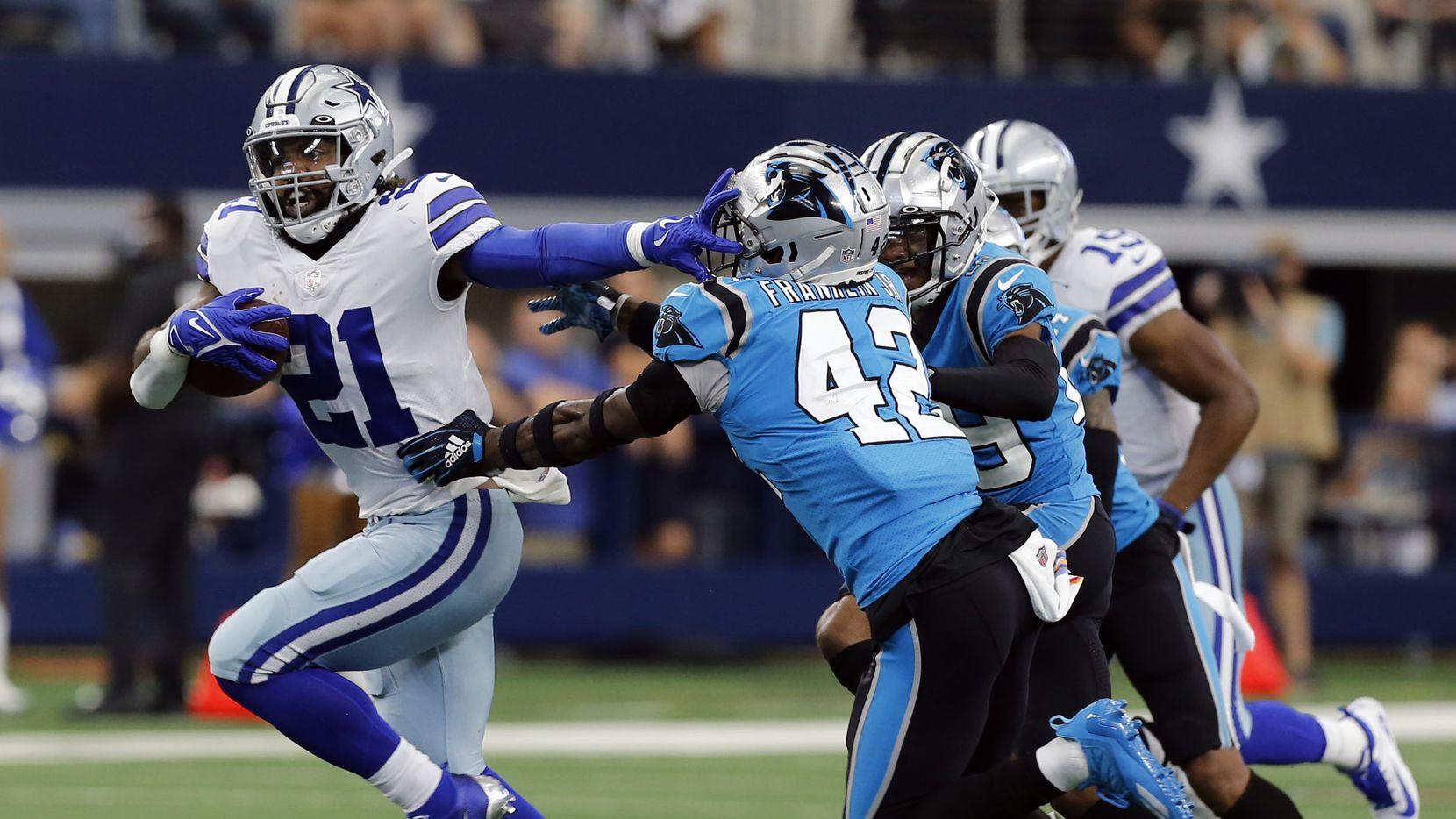 El corredor de los Cowboys, Ezekiel Elliott (izq), se quita las tacleadas delos defensivos de los Panthers de Carolina en el juego del 3 de octubre de 2021 en AT&T Stadium.