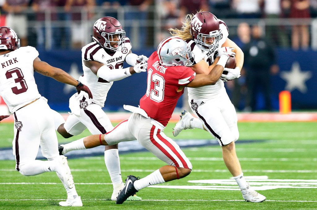 Texas A&M Aggies linebacker Cullen Gillaspia (12) returns an onside kick as he is tackled by Arkansas Razorbacks defensive back Nate Dalton (13) in the fourth quarter at AT&T Stadium in Arlington, Saturday, September 23 2017. The Aggies won in overtime, 50-43. (Tom Fox/The Dallas Morning News)