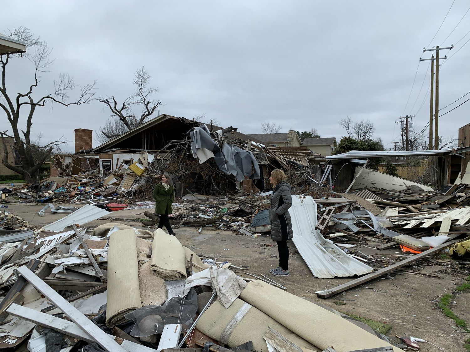 Council member Jennifer Staubach Gates, right, and her council liaison Sarah Evans tour tornado damage on Jan. 29, 2020, behind the Marsh Lane Plaza shopping center in northwest Dallas.