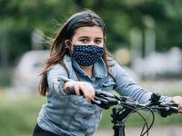 Una niña con un tapabocas pedalea una bicicleta en un parque.