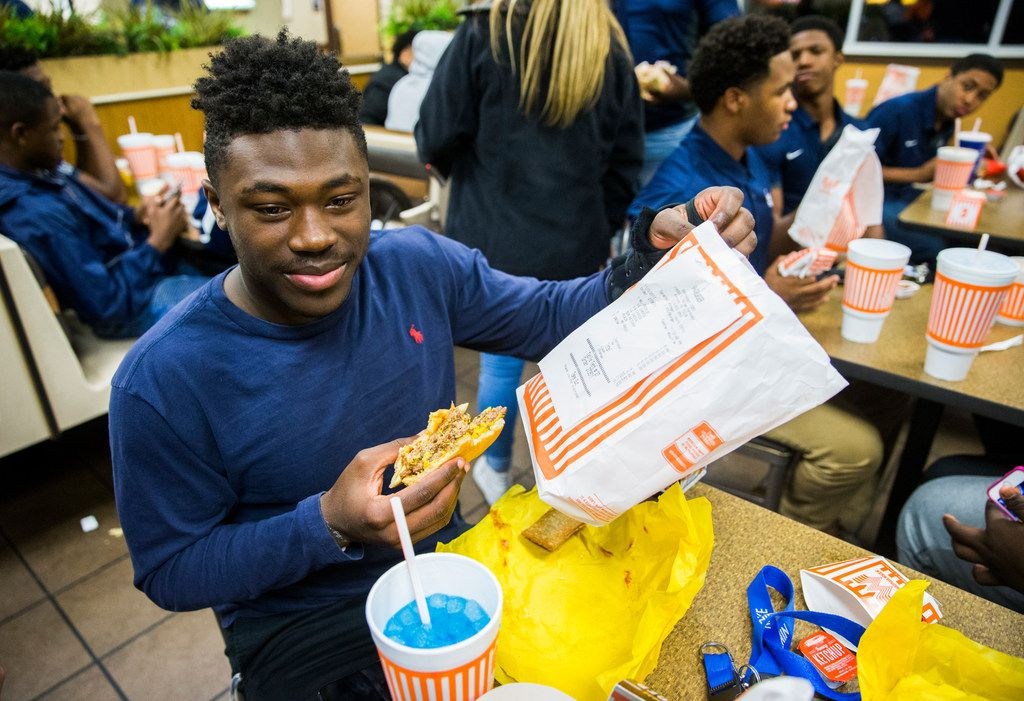 """Lone Star High School football player Darrin Smith, 16, holds up the receipt for his triple burger with fries as he and his classmates celebrate their district football title at Whataburger #1020 on Friday, November 3, 2017 at the corner of N Dallas Parkway and Eldorado Parkway in Frisco, Texas. Lone Star and Reedy High Schools played in the district championship game on Friday night. The two schools dubbed the game the """"Whatabowl"""" to determine which school """"owned"""" the Whataburger location where both school's students gather on Friday nights."""