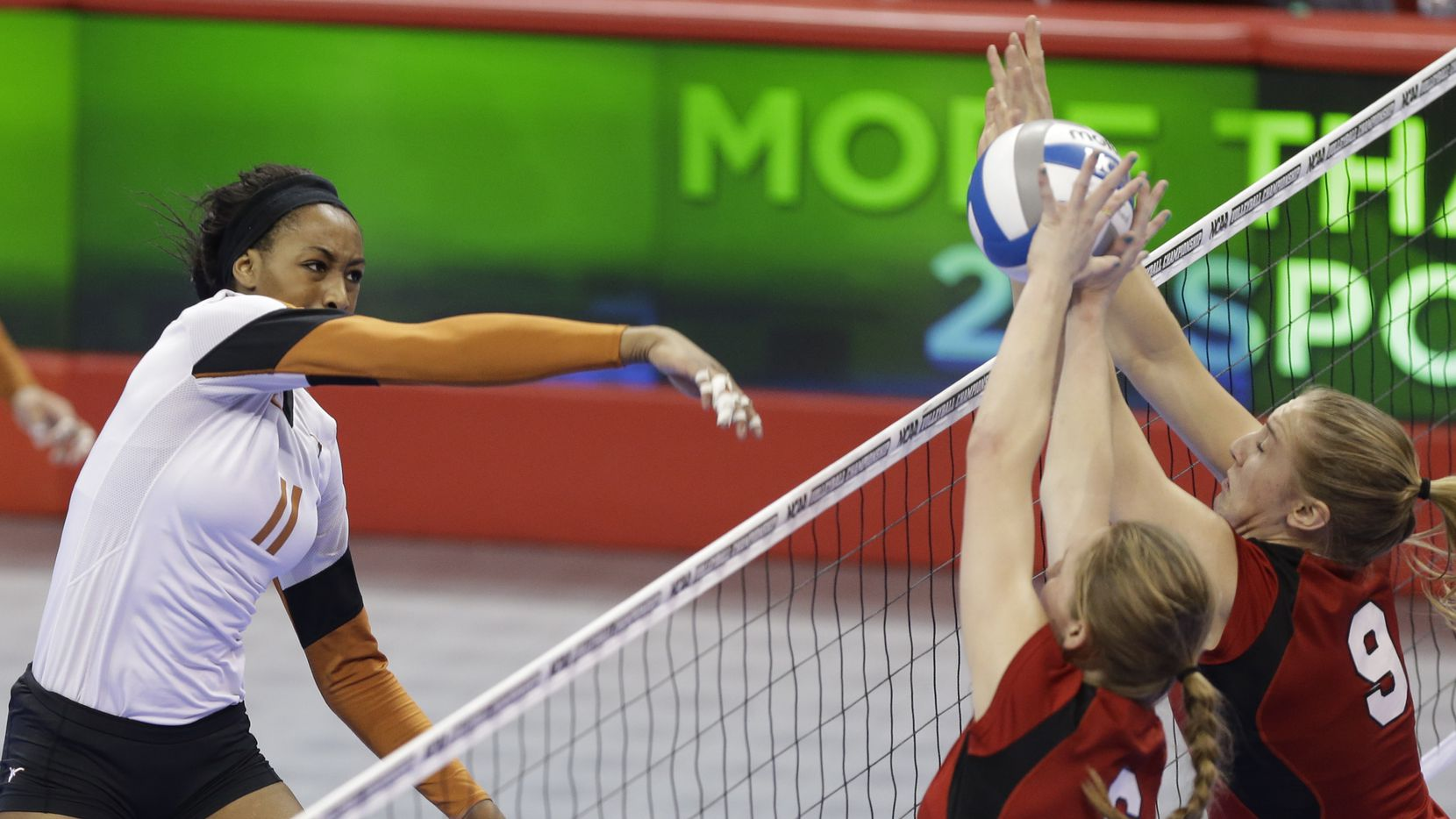 Texas' Chiaka Ogbogu (11) goes for a kill against the block of Nebraska's Kadie Rolfzen (6) and Cecilia Hall (9) in the finals of an NCAA college volleyball regional tournament in Lincoln, Neb., Saturday, Dec. 14, 2013. Texas beat Nebraska in three sets.