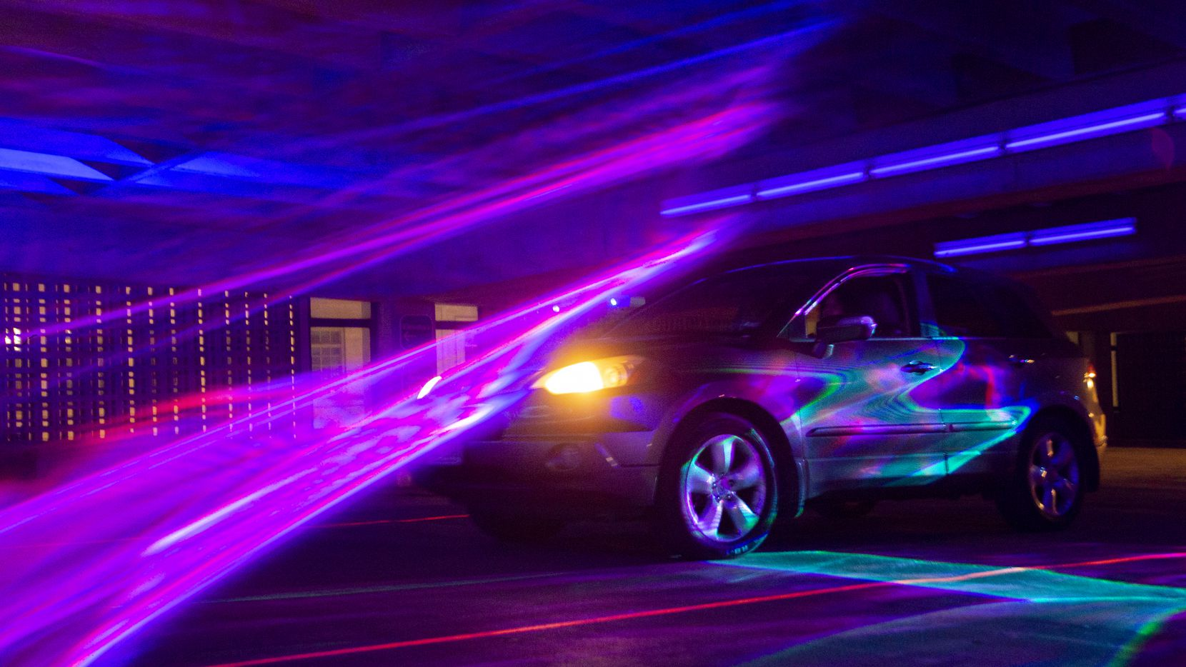 "A car passes through Melanie Clemmons and Zak Loyd's ""Laser Wash"" in Area 3 as part of the art festival Aurora in the DalPark Parking garage in downtown Dallas in October last year. Much like the Aurora festival has been impacted by COVID-19, so have local artists who can currently apply to receive a grant from the organization."