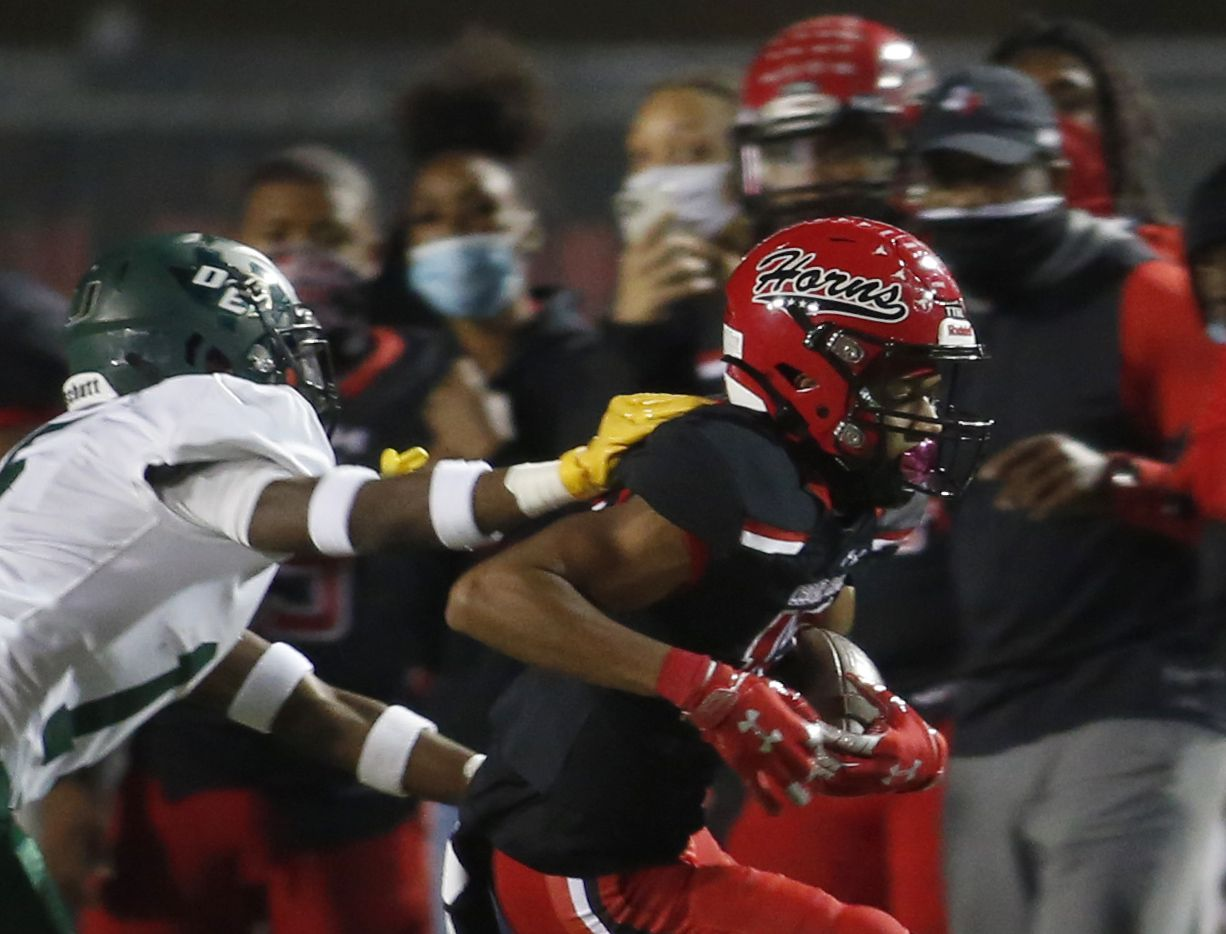 Cedar Hill Longhorns receiver Javien Clemmer (13) tacks on yardage after a reception as DeSoto defensive back Ashton Levells-Mitchell (15) moves in to force him out of bounds during second quarter action. The two teams played their District 11-6A  football game at Longhorn Stadium in Cedar Hill on November 6, 2020.