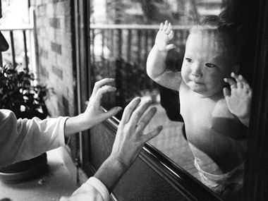 Separated by a window pane, a mother playfully taps on the glass while her child watches.