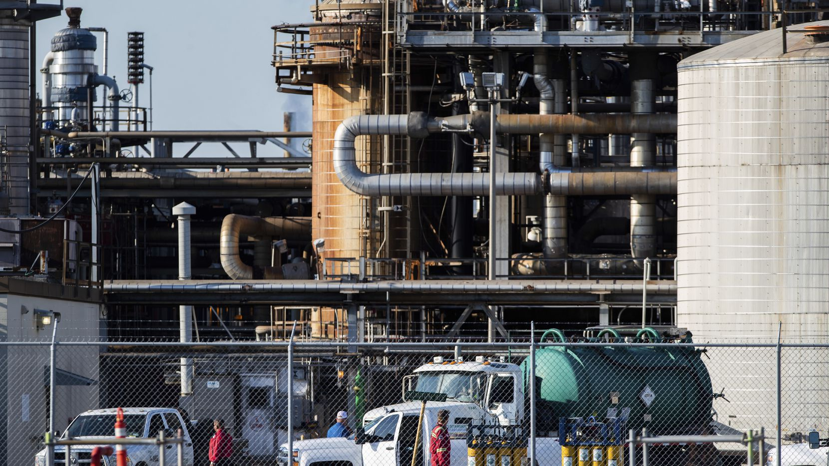 Workers stand in a lot at a LyondellBasell facility in La Porte. A chemical leak Tuesday evening killed two people at the facility and left dozens more hospitalized.
