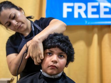 Jacob Lopez, 8, receives a free haircut from Sharon Garcia during the 23rd annual Mayor's Back to School Fair at the Fair Park Centennial Hall in Dallas in 2019. The Irving-based Living Legends Foundation will offer free haircuts, backpacks and school supplies this weekend to Dallas and Fort Worth children.