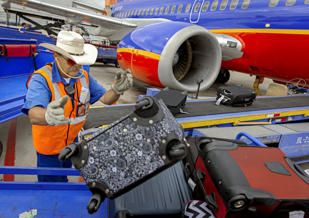 Southwest Airlines employee Frank Alfano unloads luggage from a plane at Dallas Love Field Airport Thursday, October 2, 2014 in Dallas. (G.J. McCarthy/The Dallas Morning News) 10122014xBIZ