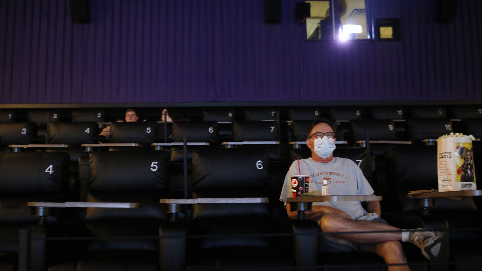 "Dan Dunham of Plano watches trailers play as he waits for ""The Invisible Man,"" to start at Cinemark West in Plano, on Friday, June 19, 2020. After a few movie theaters opened earlier this summer, theater chains are opening en-masse this weekend."