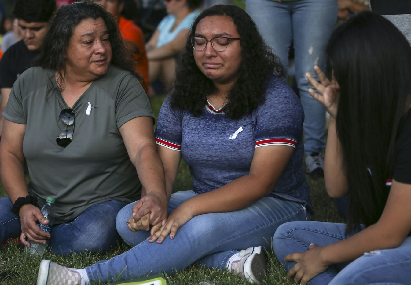 Christina Lopez (from left) comforts her daughter, Celia Lopez, 15, and Sajeili Carrasco, 15, who were both friends with Leilah Hernandez, a 15-year-old Odessa High sophomore killed in the attack, as community members gather for a prayer vigil at the University of Texas Permian Basin on Sunday, Sept. 1, 2019.