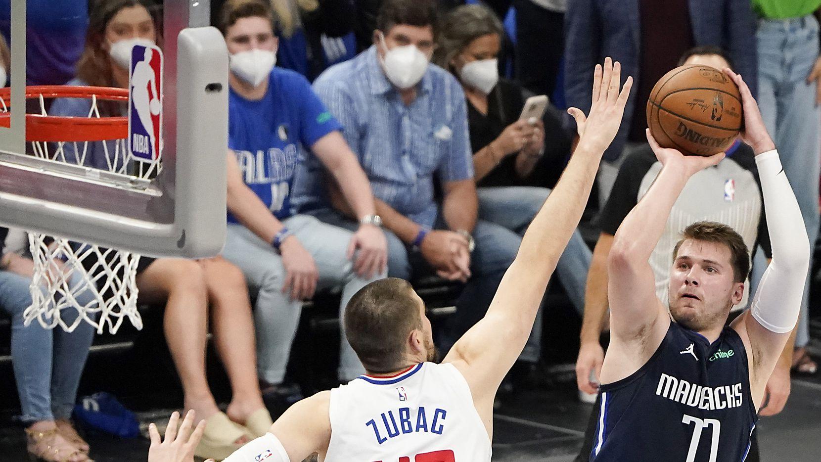 Luka Doncic (77), guardia de los Mavericks de Dallas lanza un tiro a la canasta sobre Ivica Zubac (40) de los Clippers de Los Ángeles.