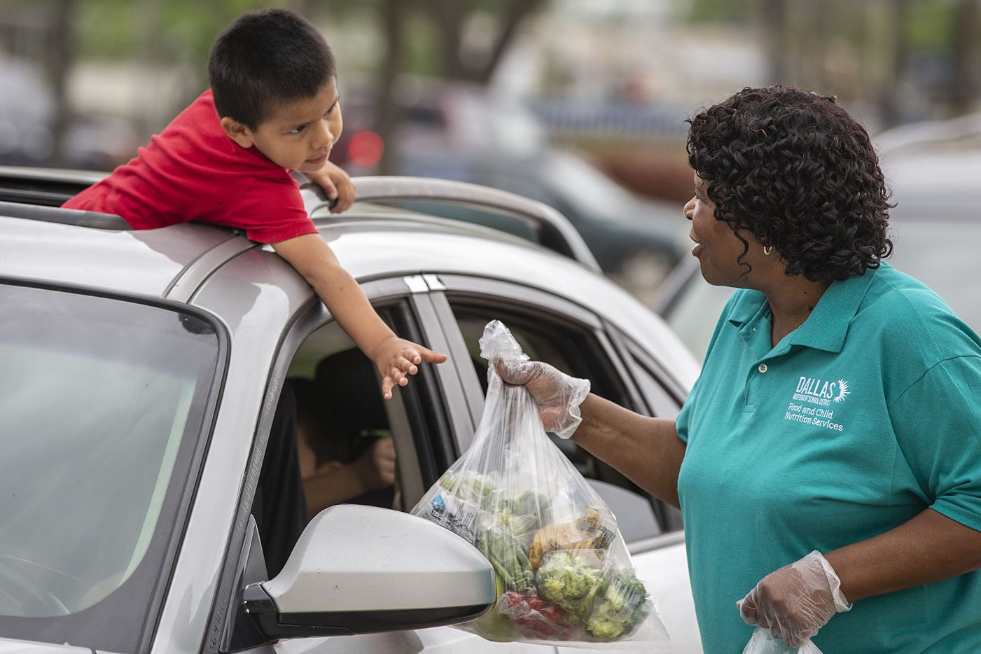 """As he hangs out of his family's car sunroof, Isaias Ovalle, 3, reaches for bagged school meals from food service supervisor Patricia Jackson at Francisco """"Pancho"""" Medrano Middle School in Dallas on Thursday, April 2, 2020. Many families of students struggle with food insecurity, exacerbated by COVID-19 closures, yet DISD announced it would eliminate Monday food distribution and limit its efforts to Thursdays only."""