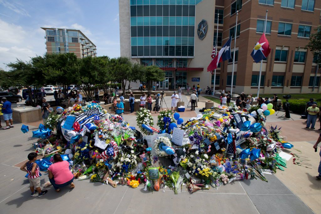 Two Dallas police cars are buried so deep in flowers and memorials that they can no longer be seen, as a memorial for the injured and slain officers from Thursday night's shooting slowly grew bigger in front of the Dallas Police Headquarters on July 9, 2016 in Dallas. (Ting Shen/The Dallas Morning News)