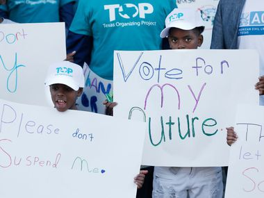 Michael Paul, 8, center, and Freddrick Washington, 11, right, attend a rally against Dallas Independent School District suspensions held by the Texas Organizing Project at the DISD Administration building, Thursday, February 23, 2017. (Brandon Wade/Special Contributor)
