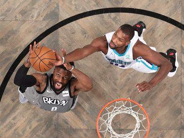 NEW YORK, NEW YORK - DECEMBER 11: David Nwaba #0 of the Brooklyn Nets and Michael Kidd-Gilchrist #14 of the Charlotte Hornets reach for the ball during the first half of a game at Barclays Center on Dec. 11, 2019, in New York City.
