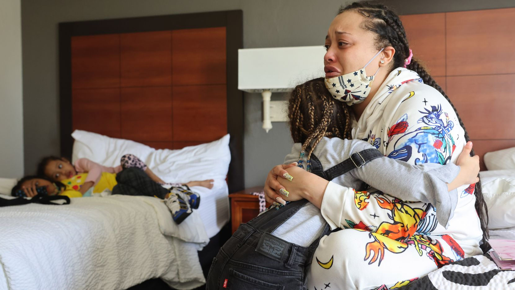 Jonnay Mckinley gets a hug from her oldest daughter, Yannoj Young, 8 as Mckinley talks about her recent eviction from her apartment while her other daughters Courtney Young, 7 and Trinity Young, 5 play with her phone inside a hotel room on Monday, February 1, 2021 in Dallas. Mckinley and her kids were evicted from her apartment Friday morning.