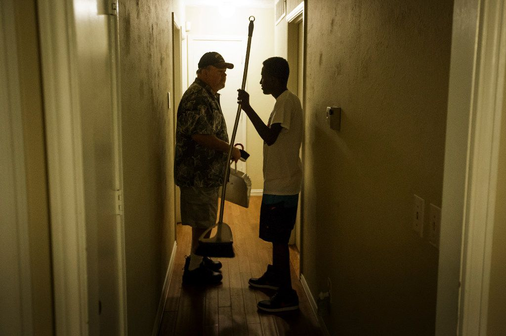 Marcos Bogale grabs a broom to help Gary Keylon clean up at the end of a going away party for Marcos and his twin brother Tamirat at the home of their host Cheryl Zapata and her family on Monday, April 24, 2017, in Plano.
