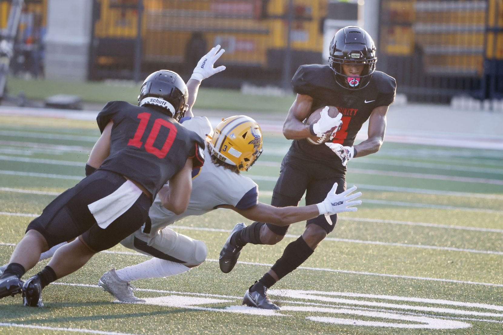 Euless Trinity defender Damarion Dean (4) returns an interception for a touchdown as teammate David Lang (10) makes a block on  an Arlington Lamar player during the first half of their high school football game in Bedford, Texas on Aug. 26, 2021. (Michael Ainsworth/Special Contributor)