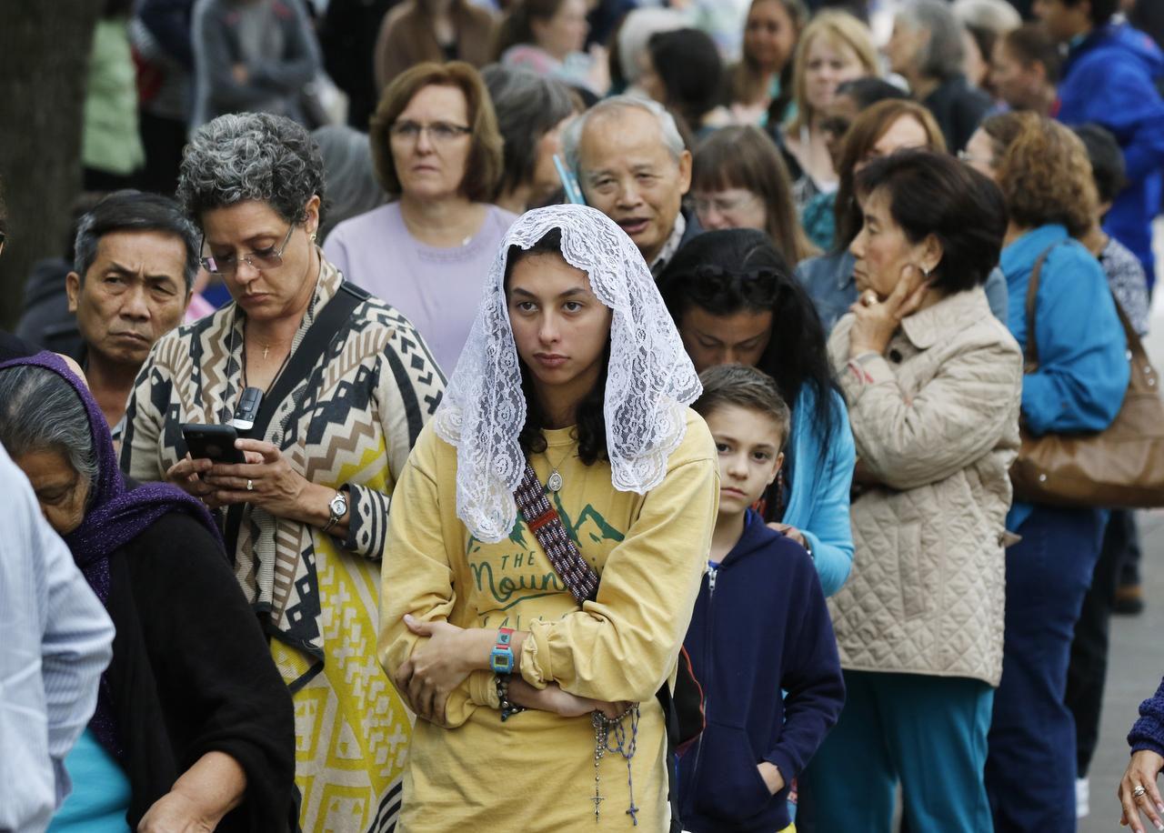 Natalie Garza (centro), de San Antonio, fue una de las miles de personas que esperaron para ver las reliquias de Santa María Goretti, en la Iglesia Católica de Santa Mónica, en Dallas. (DMN/FOTOS: DAVID WOO)