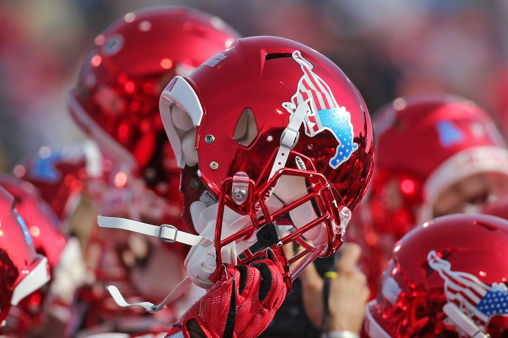 The SMU players hold their helmets high during warmups during the Navy Midshipmen vs. the SMU Mustangs NCAA football game at Ford Stadium in Dallas on Saturday, November 26, 2016. (Louis DeLuca/The Dallas Morning News)