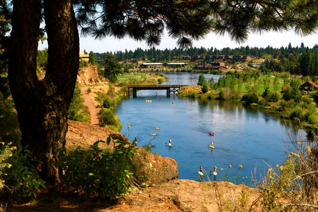 Popular pastimes include kayaking, canoeing, paddleboarding, surfing or just sitting by the Deschutes River, which flows through Bend. This photograph depicts part of the river near Bend's Old Mill District.