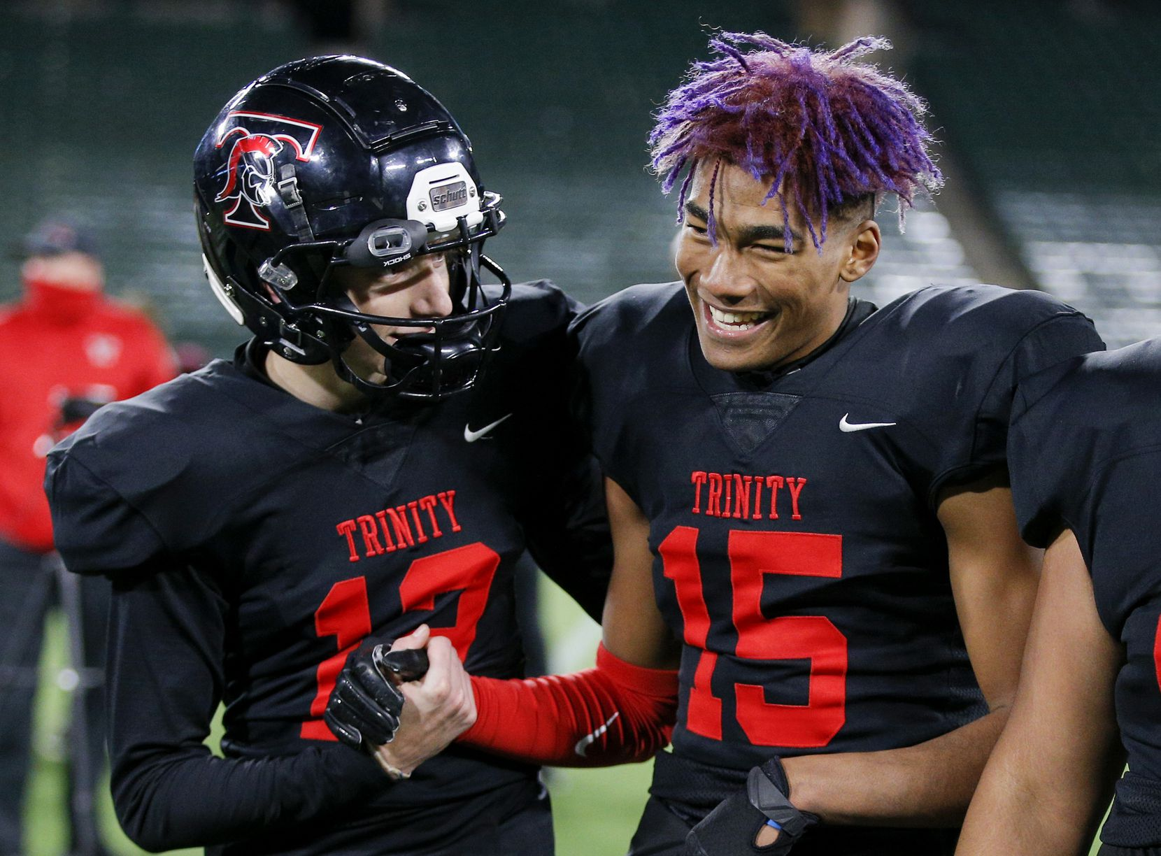 Euless Trinity junior quarterback Cade Barthelemess (12) and junior wide receiver Pofele Ashlock (15) celebrate a 49-45 win over Allen after a high school Class 6A Division I Region I semifinal football game at Globe Life Park in Arlington, Saturday, December 26, 2020. Trinity won 49-45. (Brandon Wade/Special Contributor)