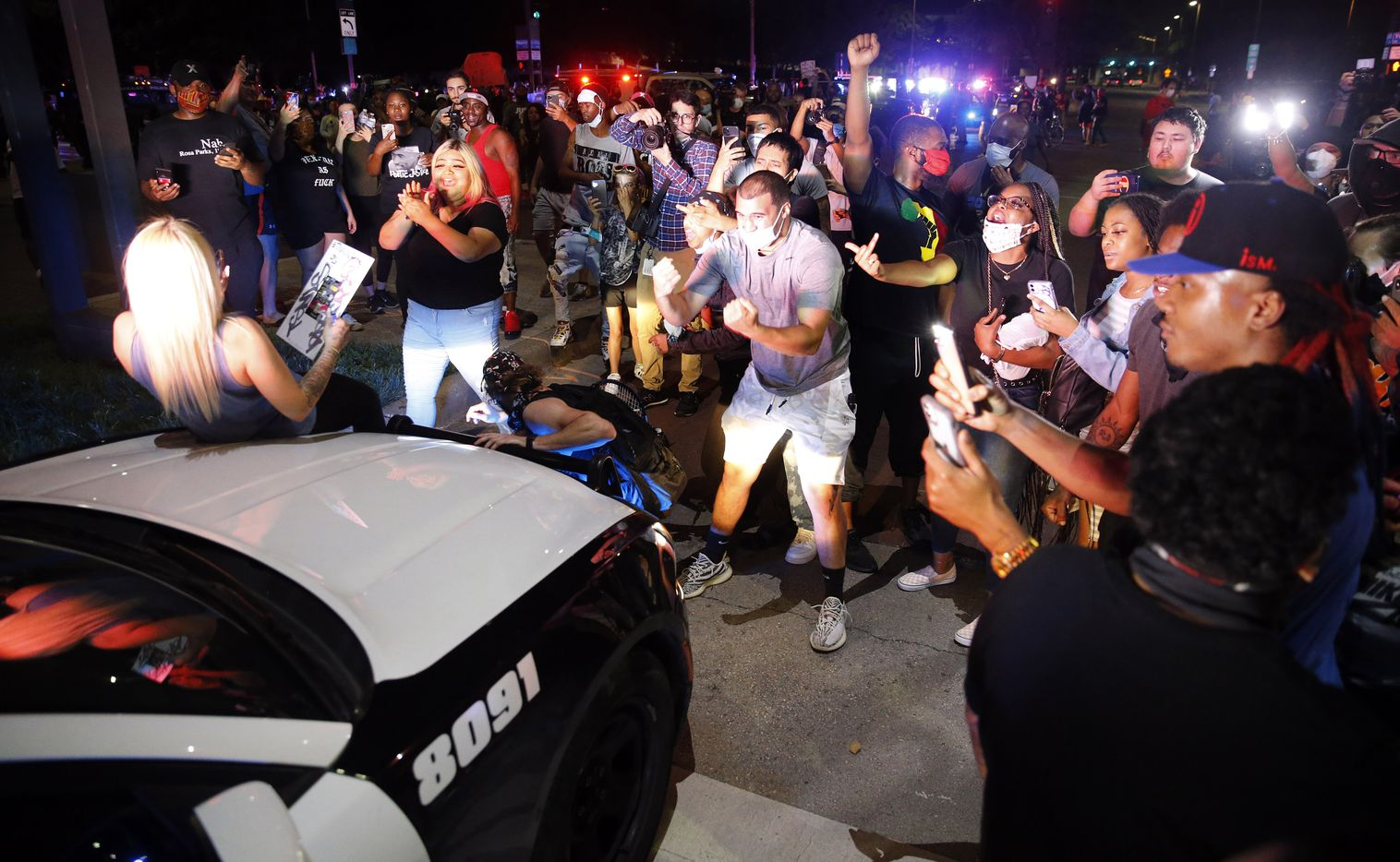 Protestors stop Dallas Police officers responding to a confrontation at Young St. and S. Griffin St. in downtown Dallas, Friday, May 29, 2020. People were marching in protest of the in-custody death of George Floyd when they confronted Dallas Police tactical officers and tear gas was fired.