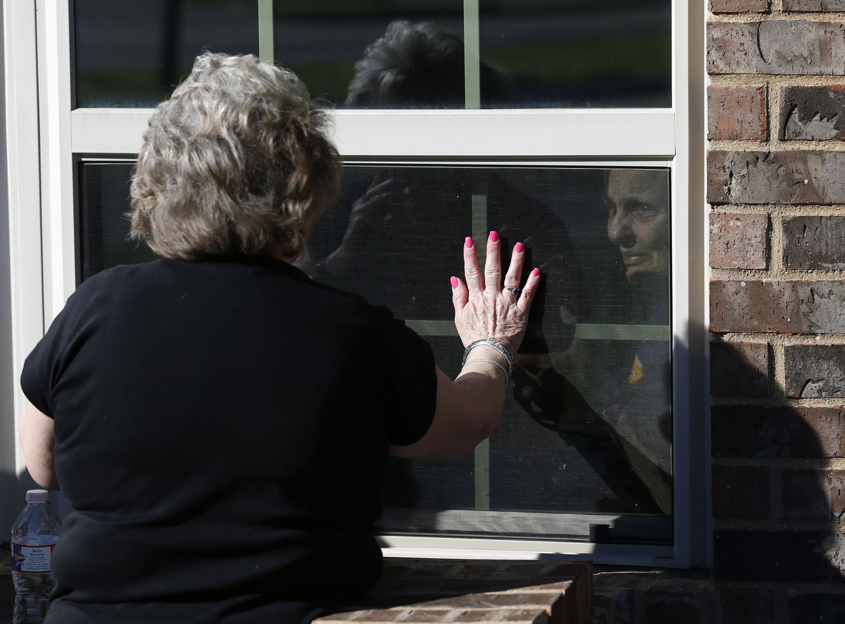 Cindy Goleman waves goodbye to her mother Peggy White from opposites sides of the window at The Pavilion at Creekwood, a healthcare and rehabilitation center in Mansfield.